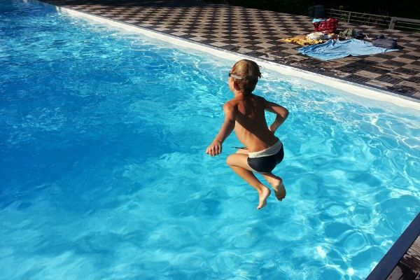 Kid jumping into swimming pool